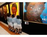 Students gather next to paintings of U.S. President Barack Obama as a child, at Obama's former elementary school in Jakarta